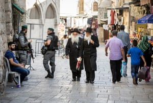 Orthodox Jews pass Israeli Defence Forces soldiers in the Muslim Quarter of the Old City