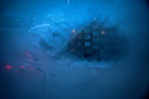 An apartment block is seen through a layer of ice on the window of a passenger minibus in the outskirts of Murmansk