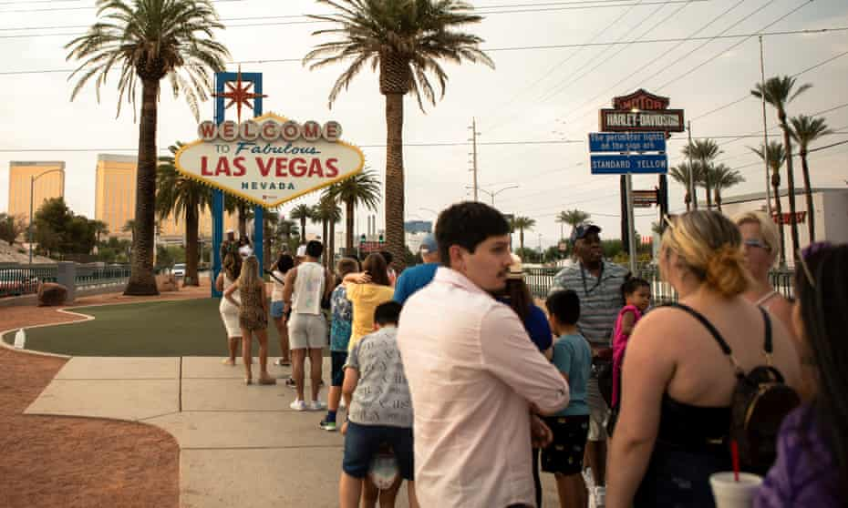 Amid a devastating heatwave, dozens of tourists wait in the oppressive temperatures to snap a selfie with the famous Las Vegas sign.