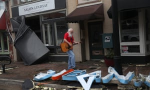 Mitch Pickering plays his guitar while walking through the downtown area after Hurricane Laura passed through on August 27, 2020 in Lake Charles, Louisiana.