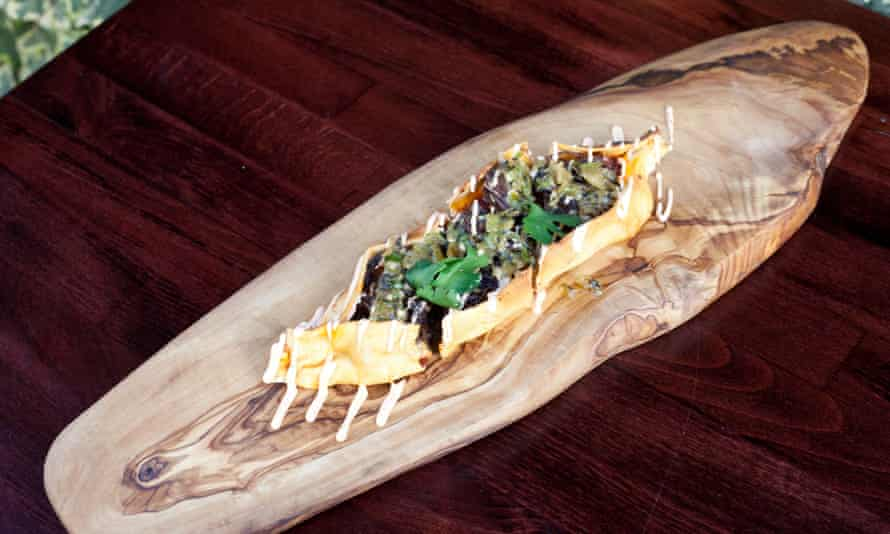 Spicy short rib pides, like small flatbread boat, on an oval-shaped rough-hewn board