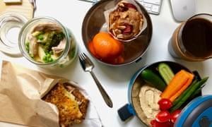 Le pack de déjeuner de bureau de Jackie Middleton, sur un bureau avec salade de pâtes aux pois, poulet et pesto, sandwich au fromage cheddar pré-grillé, crudités et houmous à tremper, un mini muffin et des fruits de saison