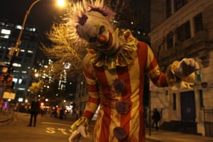 A clown poses for a photograph as he waits for the start of the Greenwich Village Halloween Parade in New York.
