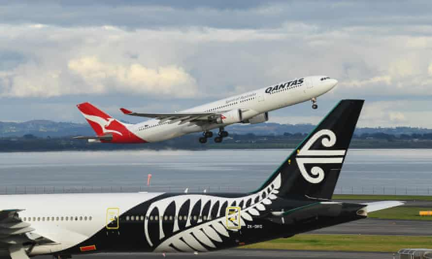 A Qantas plane takes off at Auckland airport destined for Sydney next to an Air New Zealand aircraft