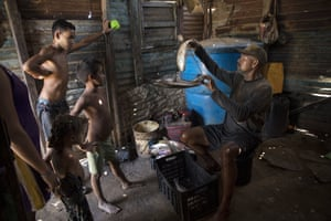 Fisherman Alejandro Elizalzabal, whose shirt is covered in oil from Lake Maracaibo, weighs his catch after a day of work on the lake