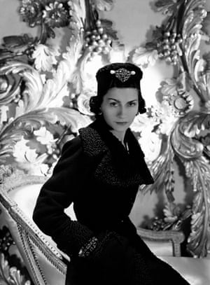 Coco Chanel wearing one of her designs: a three-quarter coat with cinched waist and astrakhan lapels and cuffs, and matching astrakhan hat with large brooch on front.