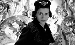 Vogue 1937: Coco Chanel wearing one of her designs: a three-quarter coat with cinched waist and astrakhan lapels and cuffs, and matching astrakhan hat with large brooch on front.