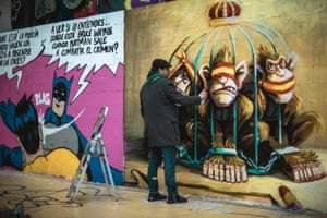 A street artist creates a mural criticising the monarchy