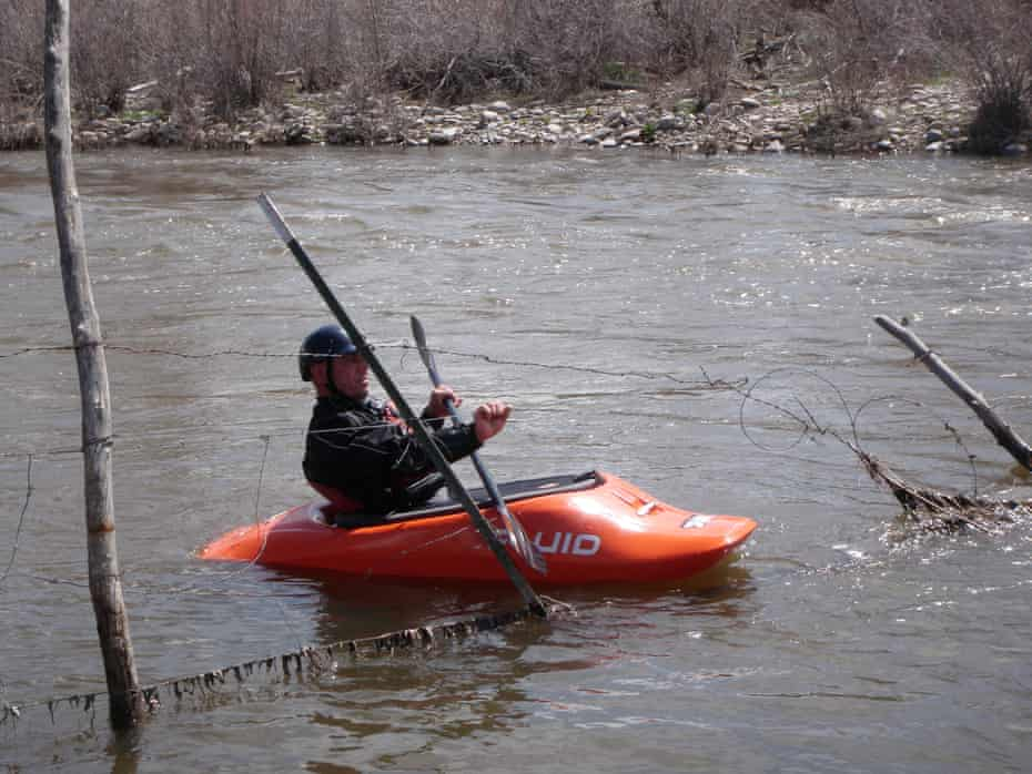 A paddler navigates through barbed wire across the Rio Chama in New Mexico.