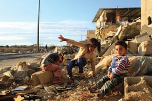 Children sit in front of their destroyed house in Khuza'a