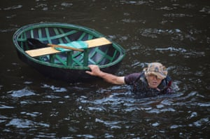 A coracler swims with his boat after falling in to the water as he takes part in the Ironbridge Coracle Regatta on the River Severn