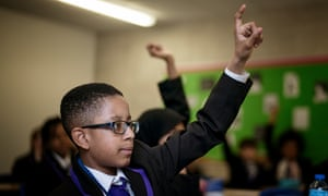 Boy in class with hand raised