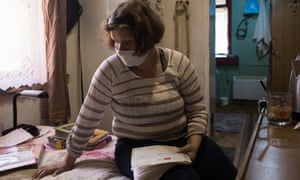 Tetiana Shulzhynska goes through her medical records at her home in Chernihiv, northern Ukraine