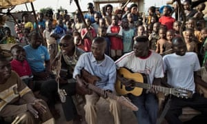 Simplice (in white Puma t-shirt) plays acoustic guitar with others in the M'Poko camp.
