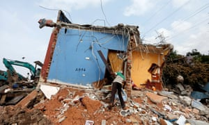 Disaster: a man at his damaged house after a garbage dump collapsed, Colombo, Sri Lanka, 18 April 2017.