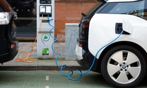 Two electric cars charging on a city street, UK.