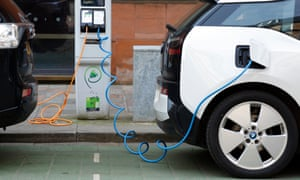 Two electric cars charging on a city street.