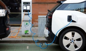 Two electric cars are topped up in Glasgow. In Scotland the average driver is three miles from a point.