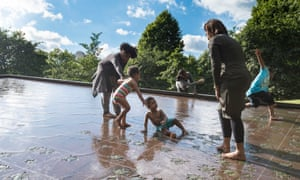 Children play in the cool water of the Canada Memorial in Green Park, London.