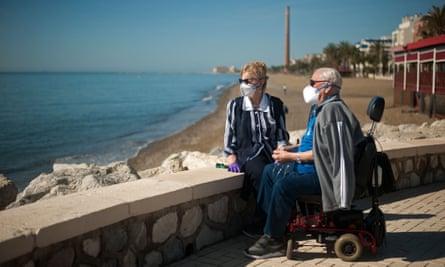 Couple wearing masks by the beach in Málaga, Spain