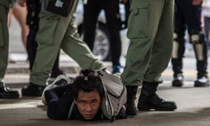Man lying on ground with hands handcuffed as legs in khaki pants and combat boots stand by