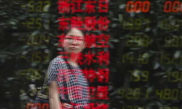 A woman is reflected on an electronic board showing stock information at a brokerage house in Shanghai.