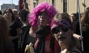 A young woman wearing a pink wig takes part in a rally, demonstrating against gender violence and calling for gender parity in Milan, Italy.