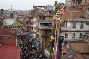 Men ride a chariot through Kathmandu during the Seto Machindranath festival