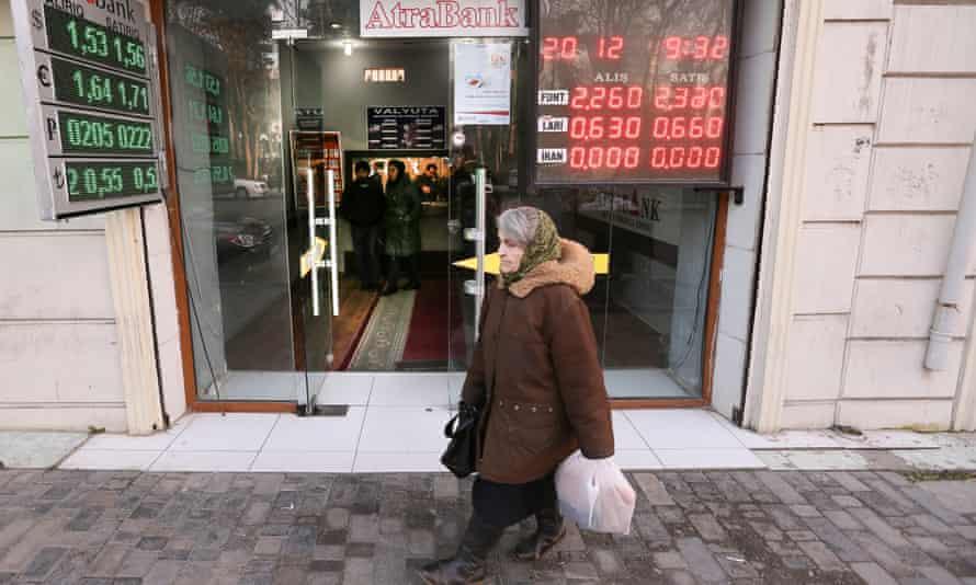 A woman walks past a money exchange office in Baku.