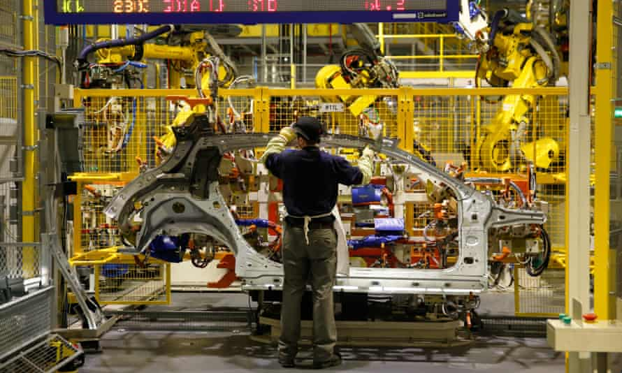 An employee handles a side panel of an Infiniti Q30 car on the production line at the Nissan plant in Sunderland.