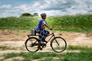 Elizabeth Kankoyo transports a 20 litre urn of milk by bike to the depot, 7km away in Zimba.