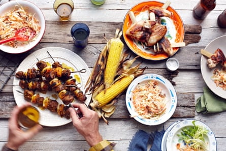 Mans hand picking up lamb and chicken skewer from tableSouth Africa Sosaties- Lamb, Curry Marinade, Dried Apricot, Grilled Corn on the Cob Japan Tebasaki Skewered Chicken Wings- Sesame Oil, Sake, Lemon, Lettuce