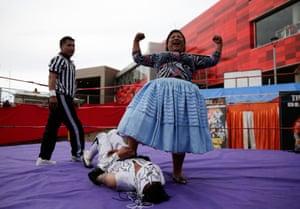 La Paz, Bolivia. A cholita wrestler, celebrates after winning a fight