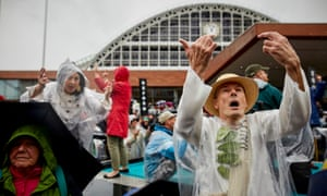 Performers wearing laurel branches – symbols of peace – brave the rain in central Manchester to mark the bicentennial of the Peterloo massacre.