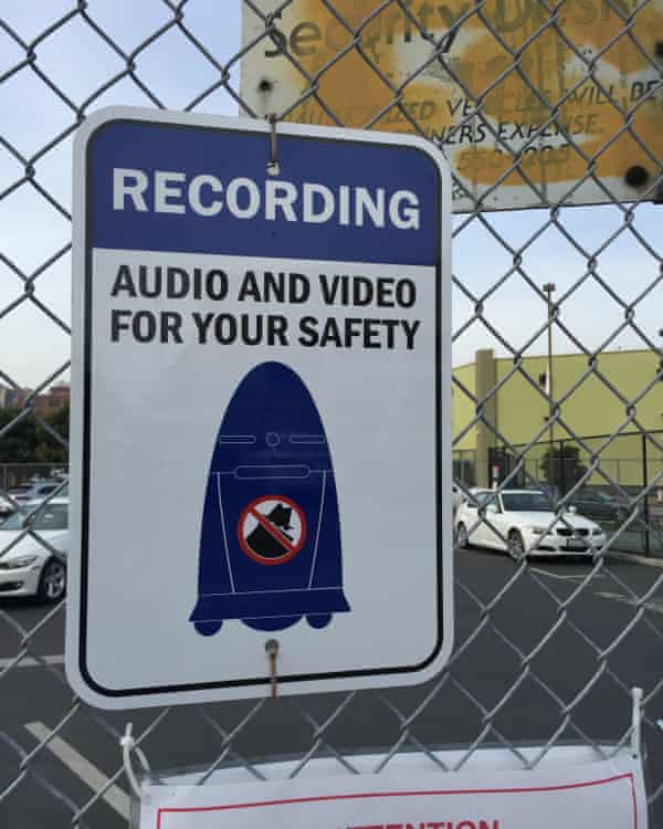 A robot-related warning on the SF SPCA parking lot fence.
