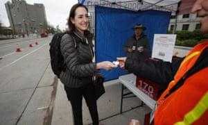 Nilufer Saltuk of Denver smiles as she gets a sticker for dropping off her ballot in Denver