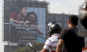 Motorists ride past a billboard displaying Facebook's Free Basics initiative in Mumbai, India, December 30, 2015.
