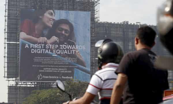 Motorists ride past a billboard displaying Facebook's Free Basics initiative in Mumbai, India, 2015.