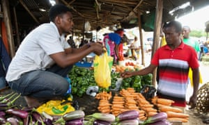 A market seller serves a customer with a plastic bag in Dar es Salaam, Tanzania, on 31 May, just before the ban came into effect on 1 June