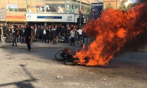 Iranian protesters gather around a burning motorcycle during a demonstration in the city of Isfahan against increased petrol prices
