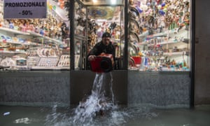 A shopkeeper bales out his store in flood-hit Venice