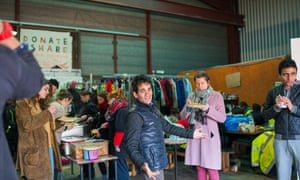 Refugees and volunteers at a warehouse run by L'Auberge des Migrants.