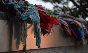 Tattered peace cranes adorn a memorial.