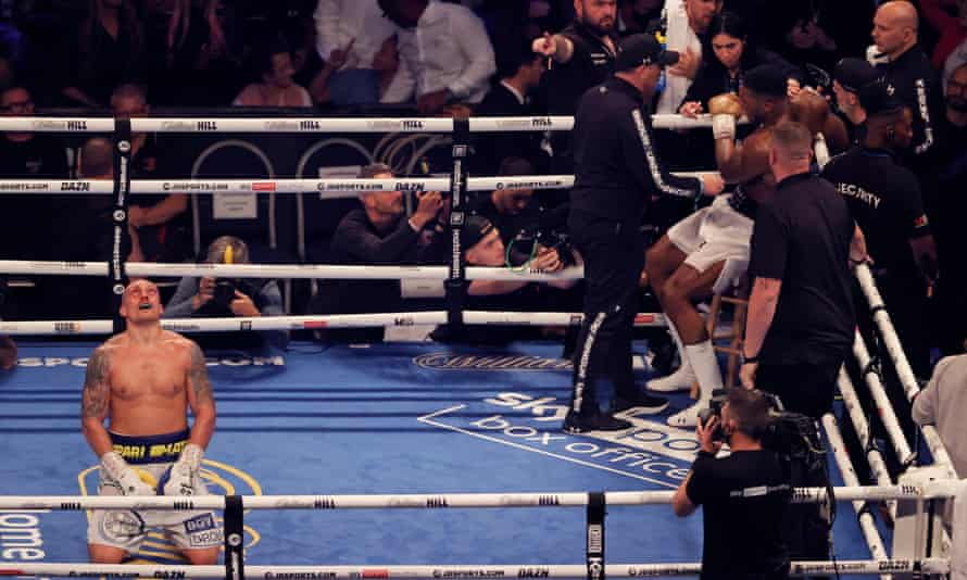 Oleksandr Usyk celebrates just after the final bell as Anthony Joshua sits in his corner
