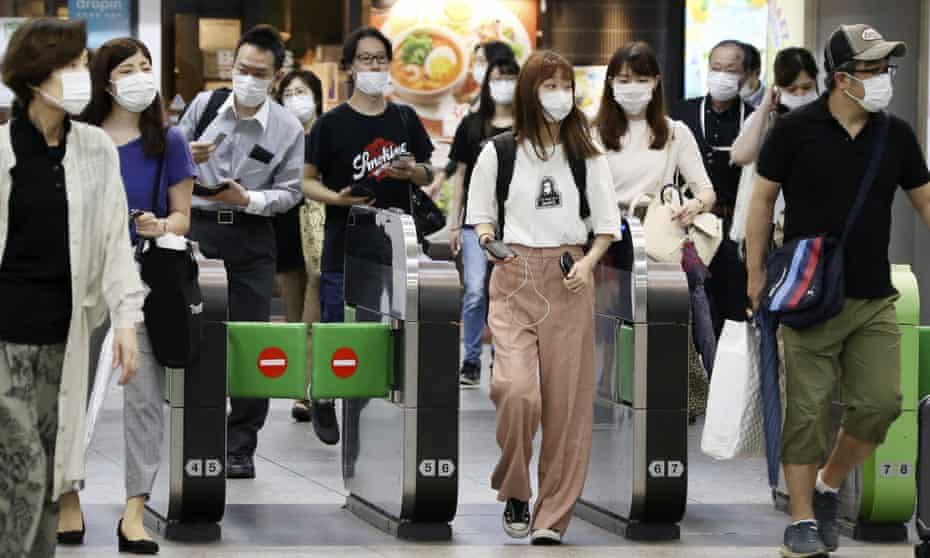Rail passengers at Yokohama station. People in Japan began to wear masks back in February.