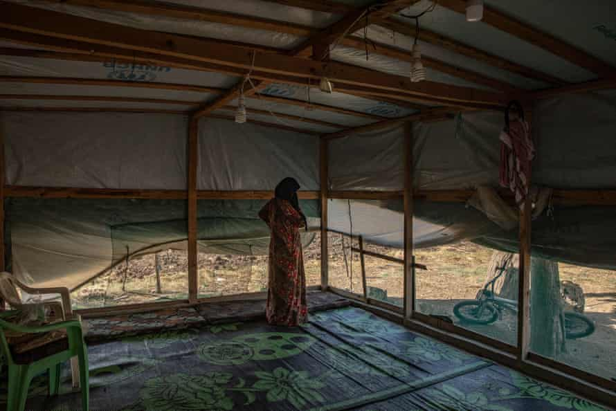 Mariam, 49, in her tent where she lives with eight other people, including her three children