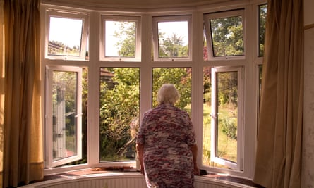 A retired woman stares out of a window