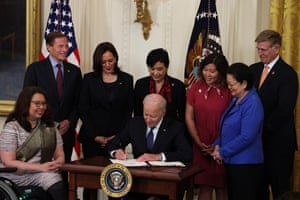 Kamala Harris and members of Congress look on as Joe Biden signs the COVID-19 Hate Crimes Act into law.