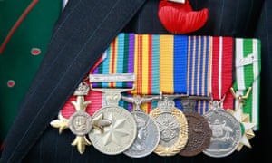 A war veteran's military service medals are displayed next to a poppy on his jacket as he attends the Dawn Service in Melbourne.