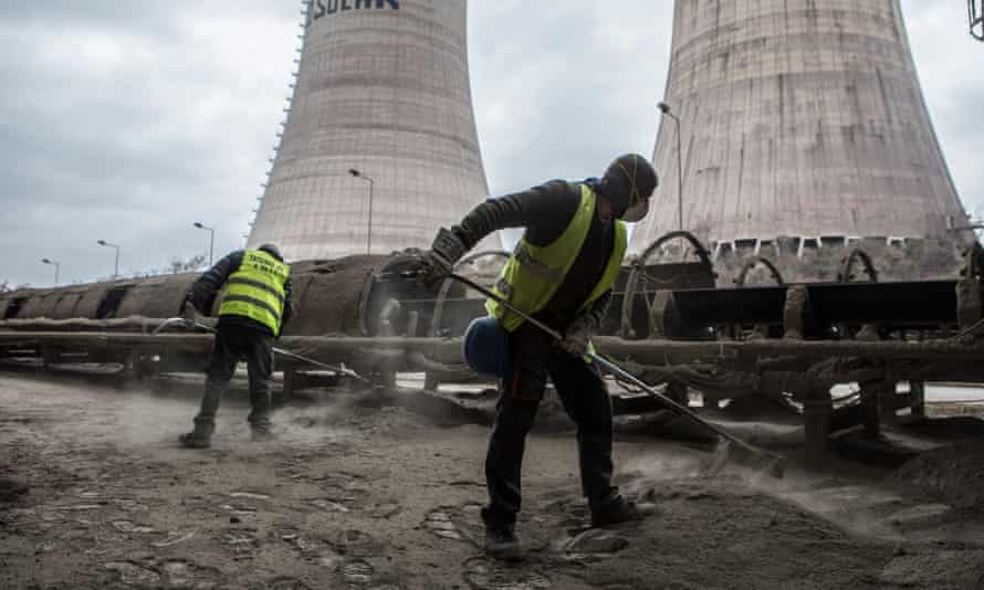 Two PPC workers clean the ash around the conveyor belt which transfers the coal.